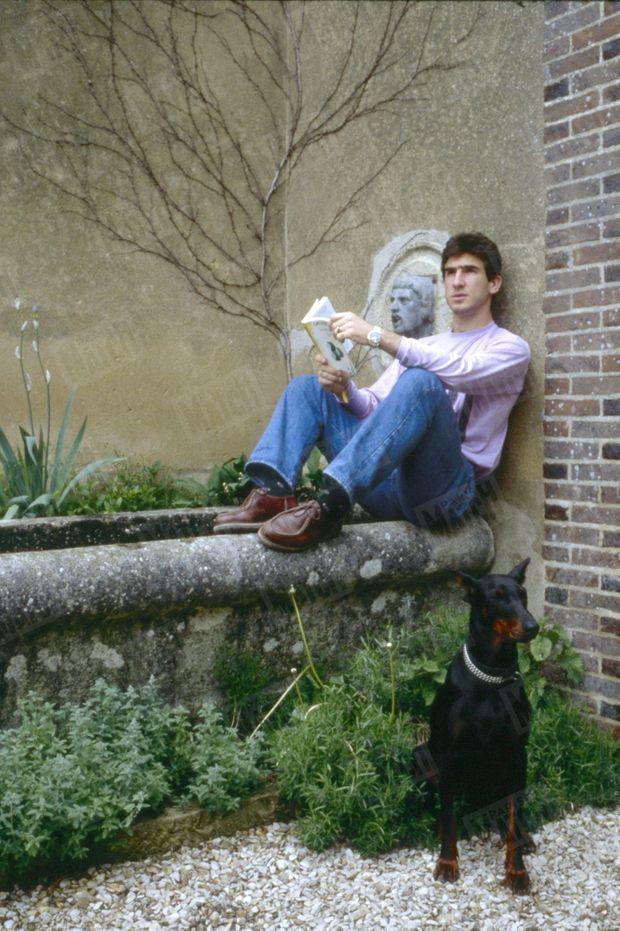 Eric Cantona dans sa maison de Poilly-sur-Tholon, près d'Auxerre, avec sa chienne Branda à ses pieds, lisant un ouvrage de psychanalyse, le 13 mai 1988.