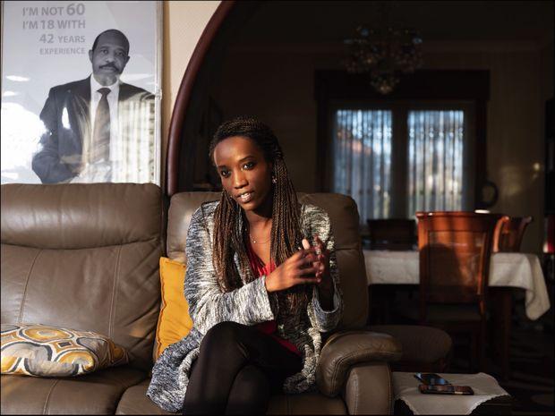Carine, 27 ans, chez elle à Bruxelles devant un portrait de son père.