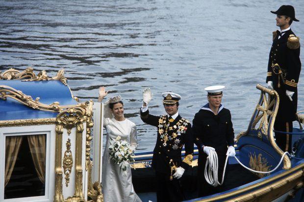 """Stockholm - 19 juin 1976 - Sur une chaloupe de style baroque nommée """"Vasaorden"""", le roi CARL-GUSTAV XVI DE SUEDE coiffé d'une casquette, aux côtés de Silvia SOMMERLATH, portant une robe DIOR et coiffée d'un diadème d'or orné de camées sertis de perles fines, saluant à l'ocassion de leur mariage Photo :"""