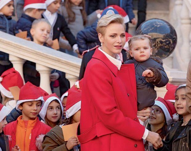 Charlène, sa fi lle dans les bras, va distribuer des cadeaux aux enfants de la principauté.