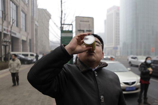 Chen Guangbiao respirant une canette d'air pur à Pékin, en 2013.