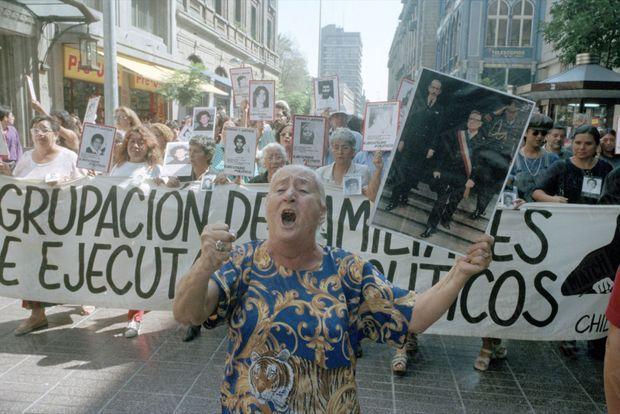 Une femme brandissant le portrait du président chilien Salvador Allende, renversé et tué par la dictature de Pinochet en 1973, lors des manifestations à Santiago après la libération par les autorités britanniques du général, en raison de son état de santé, en mars 2000.