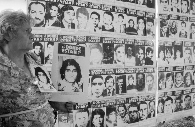 Une femme tenant le portrait d'un proche, près d'un mur de photos de personnes disparues sous la dictature de Pinochet, lors des manifestations à Santiago du Chili, après la libération par les autorités britanniques du général en raison de son état de santé, en mars 2000.