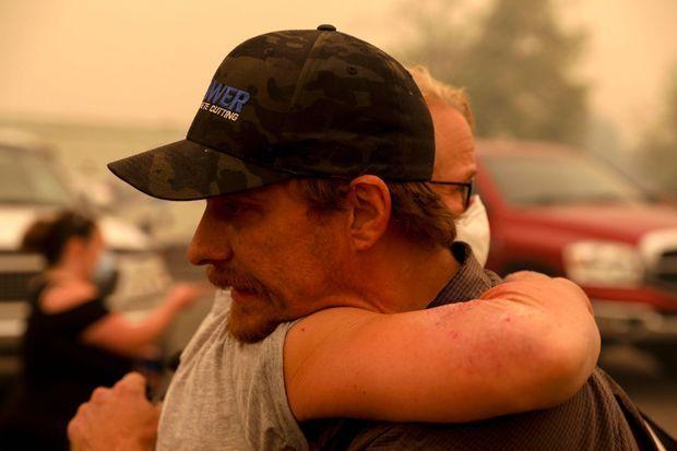 Chris Tofte prend dans ses bras une personne aidant aux recherches de son fils.