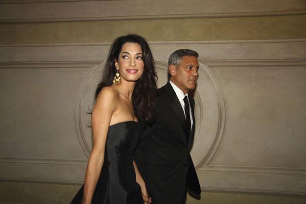 Arrivée au Palazzo Vecchio. Amal porte une robe longue bustier en satin noir Dolce & Gabbana. Pour seule parure, une paire de boucles d'oreilles en or.