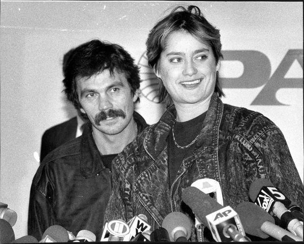 """Nadia Comaneci lors d'une conférence de presse à son arrivée à l'aéroport JFK de New York, le 1er décembre 1989. Derrière elle, son """"ami"""" Constantin Panait."""