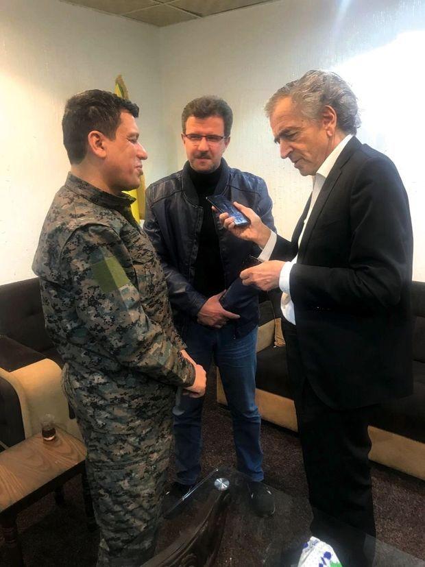 Conversation téléphonique entre le président Macron, Mazloum Abdi, le chef militaire kurde dont la tête est mise à prix par la Turquie, et BHL. Au milieu, l'interprète.