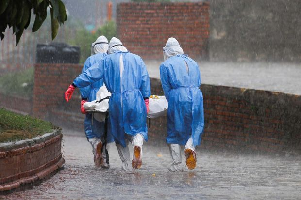 Des membres de l'armée népalaise portent le corps d'une personne décédée des suites du coronavirus, sous la pluie au crématorium, à Katmandou.