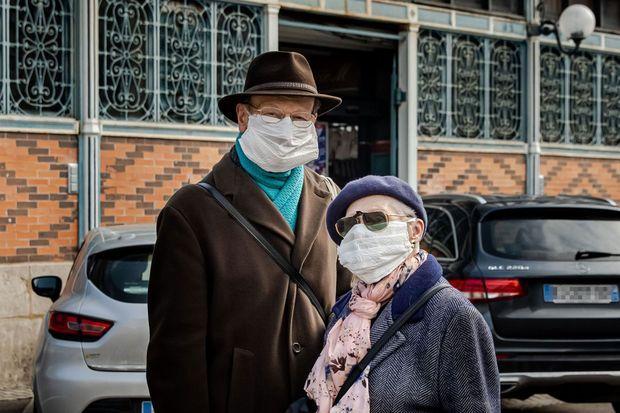 A Dijon, le 26 mars, un couple porte des masques confectionnés à partir de feuilles d'essuie-tout.