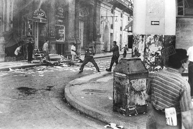 Cuba, 1959, Duel au pistolet entre un révolutionnaire castriste et un policier de Batista. Les « barbudos » entrent dans La Havane le 1er janvier 1959. Le dictateur cubain Fulgencio Batista est en fuite. En voyage de noces sur l'île, nos journalistes Marie-Hélène Viviès et Daniel Camus assistent à la marche triomphale du « libertador » Fidel Castro. Dans la capitale en proie aux exactions, le photographe de Paris Match saisit ce duel au pistolet.