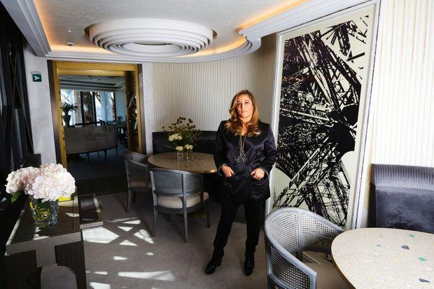 Dans l'alcôve entre deux salles, Aline Asmar d'Amman devant une photographie de Karl Lagerfeld.