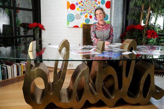 Delphine et la table de verre de sa salle de séjour, sur un socle « Blabla » – l'un de ses leitmotivs, aujourd'hui une signature.