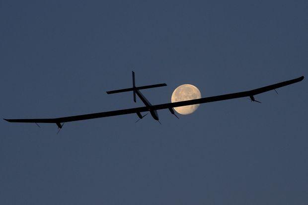 Solar Impulse en vol avec la Lune en arrière plan.