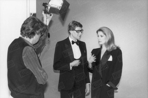 En 1981, Catherine Deneuve fête les 20 ans de carrière d'Yves Saint Laurent en posant dans ses robes, photographiée par Helmut Newton.