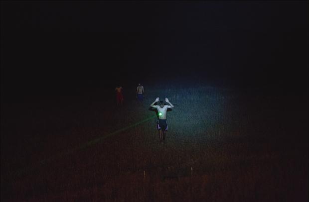 Depuis le haut de la tranchée, un rayon laser est pointé sur un réfugié.