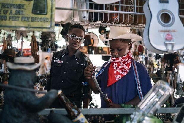 Des enfants, spectateurs du rodéo, s'amusent avec des objets de cow-boys, chapeaux et pistolets en plastique en vente sur les stands des exposants