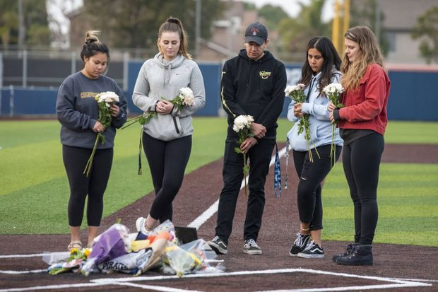 Des étudiantes du Orange Coast College rendent hommage au coach John Altobelli.