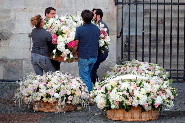 Des gerbes de fleurs devant l'église Saint-Sulpice à Paris, lundi.