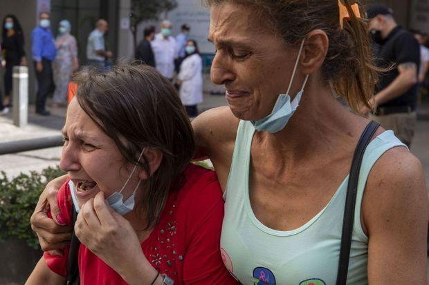 Deux employées réagissent après le licenciement de centaines de personnes à l'hôpital de l'Université américaine de Beyrouth.