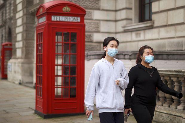Deux femmes portant un masque marchent à Londres.