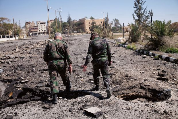 Deux généraux dans la ville moderne, Tadmor, près du cratère d'une mine explosée par les démineurs russes.