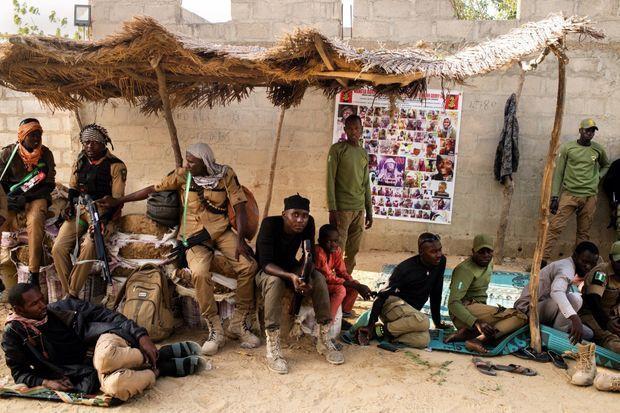 Devant la maison de leur chef Maidroma, à Maiduguri, à quelques kilomètres des bastions de Boko Haram, le 7 mars. Sur l'affiche, les visages des terroristes recherchés, dont Abubakar Shekau, leader de la secte djihadiste.