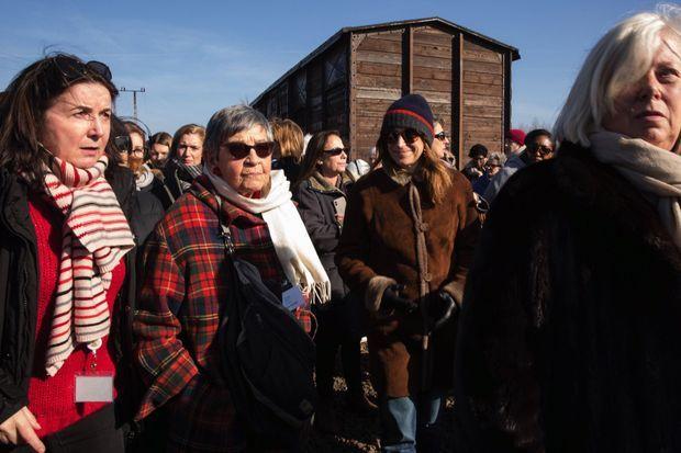 Devant un wagon semblable à celui dans lequel elle a été déportée, Ginette Kolinka et les visiteuses de l'association Langage de femmes, le 17 février