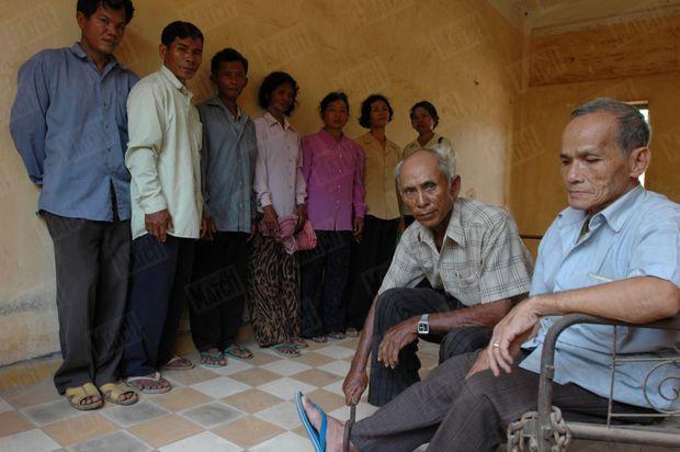 «Chum Mey, 74 ans, montre sur une autre victime, Bou Meng, 64 ans, comment les Khmers rouges attachaient au sol les chevilles des suspects à leur entrée dans la salle de torture. Le long du mur, 7 anciens gardiens de S21 (de g. à dr.): Nuon Hong; Him Huy; Peng Kry; My Chan; Orn Sav; Lo Sim et Rath Nim. Tous ont aujourd'hui entre 48 et 53 ans. Ils étaient des adolescents quand ils terrorisaient les détenus du camp.» - Paris Match n°2913, 17 mars 2005
