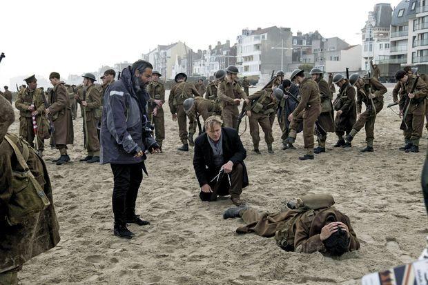 Pendant le tournage, sur la plage de Dunkerque. Le réalisateur Christopher Nolan, accroupi au centre.
