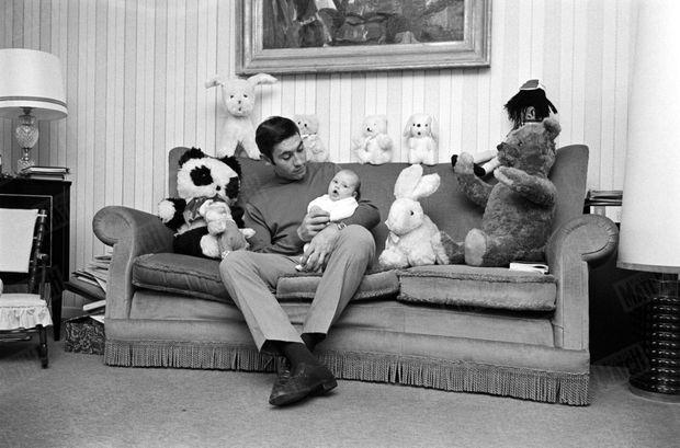 Eddy Merckx en avril 1970, chez lui a Tervuren, assis sur le canapé avec sa fille Sabrina bébé dans les bras, au milieu d'animaux en peluche. A chacune de ses victoires, Eddy ramène une nouvelle peluche pour Sabrina.