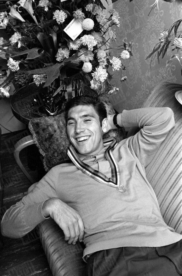 Eddy Merckx en mars 1966, dans la maison de ses parents à Woluwe-Saint-Pierre, en Belgique. Il pose avec sa médaille de champion autour du cou. Il vient de remporter la 57e édition de la course cycliste San Remo-Milan.