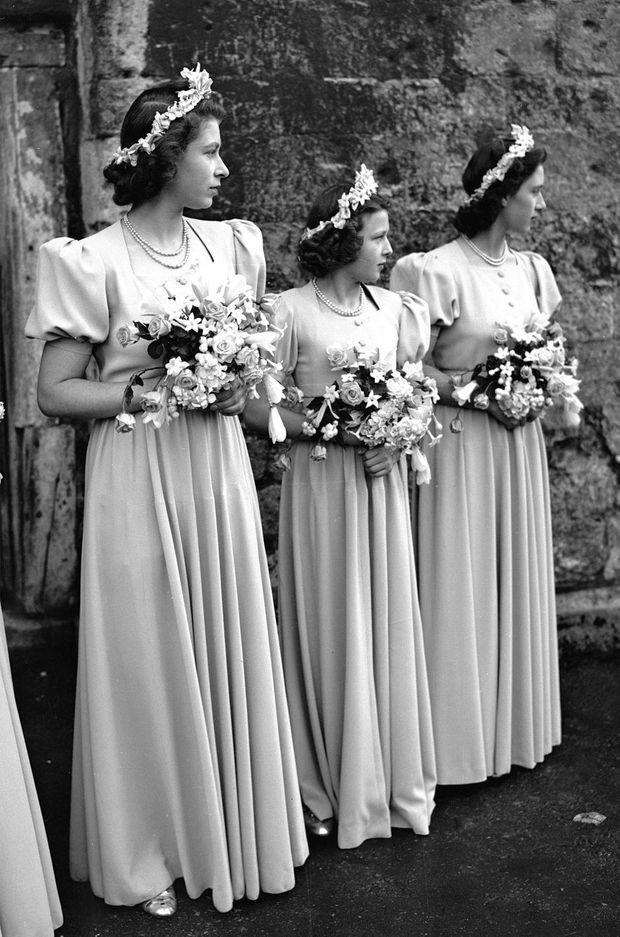 La princesse Elizabeth et sa soeur la princesse Margaret entourent la princesse Alexandra de Kent, au mariage de Patricia Mountbatten, le 26 octobre 1946