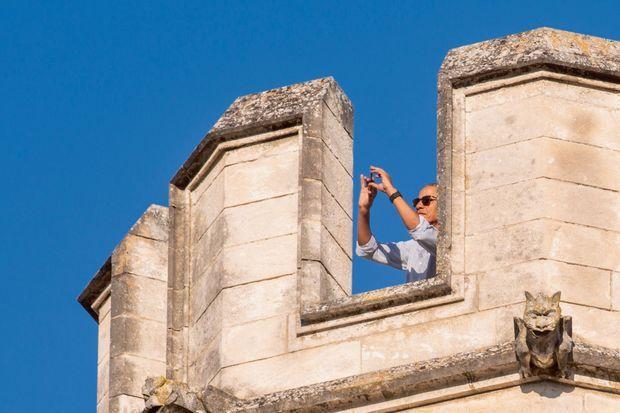 Entre les créneaux d'une tour du Palais des Papes. Non pas un archer mais un ancien président armé de son Smartphone.