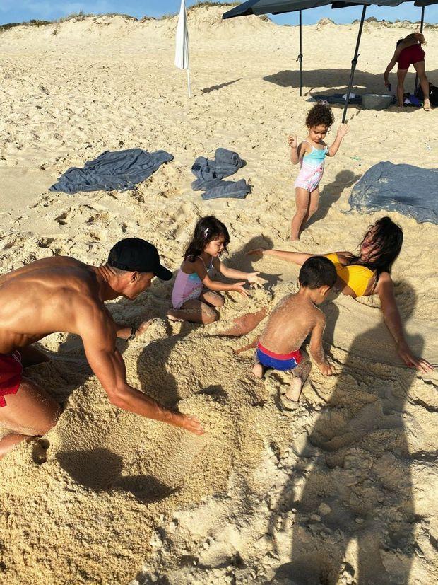 Escale sur la plage de Comporta (Portugal). Georgina est recouverte de sable par les jumeaux Eva et Mateo avec l'aide de Ronaldo, sous les yeux rieurs d'Alana Martina.