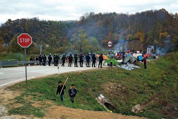 Face aux policiers bosniaques, le camp improvisé des migrants.