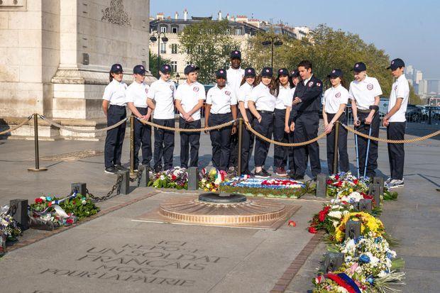 Les volontaires du SNU et le secrétaire d'Etat Attal au pied de l'Arc de Triomphe.