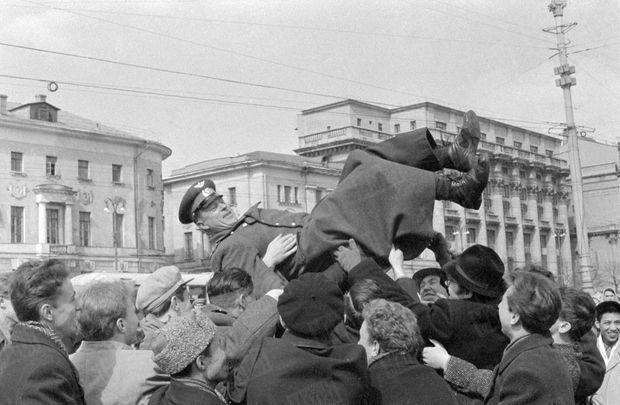 """« """"Gloire ! Gloire ! Nos cœurs t'accompagnent !"""" Tout Moscou chante ce refrain créé en l'honneur de Gagarine. le premier homme du cosmos. Depuis la journée historique du 12 avril, la capitale soviétique exulte et la gloire de Gagarine fait du moindre aviateur le héros du jour : dès qu'elle voit l'uniforme de l'armée de l'Air, la foule s'empare de celui qui le porte, le soulève à bout de bras et lui fait faire le vol plané de l'enthousiasme. » - Paris Match n°628, 22 avril 1961"""
