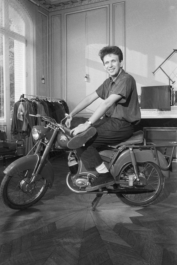 Le couturier Jean Paul Gaultier, 30 ans, posant au milieu de son appartement, sur sa moto Rhonson, le 21 juillet 1982.