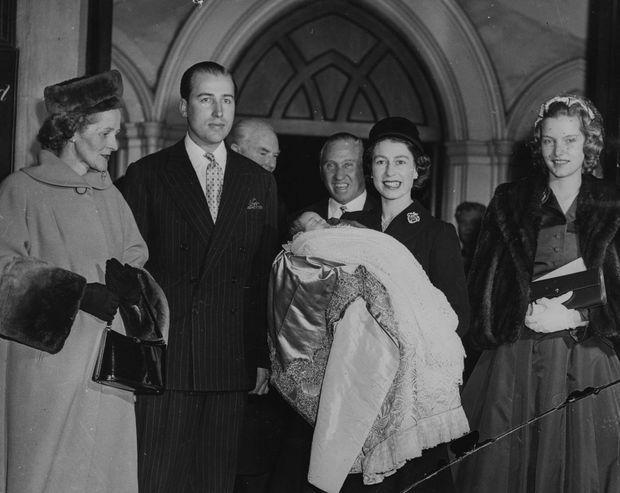 La reine Elizabeth II avec Lord et Lady Porchester lors du baptême de leur fils George Herbert, le 12 décembre 1956