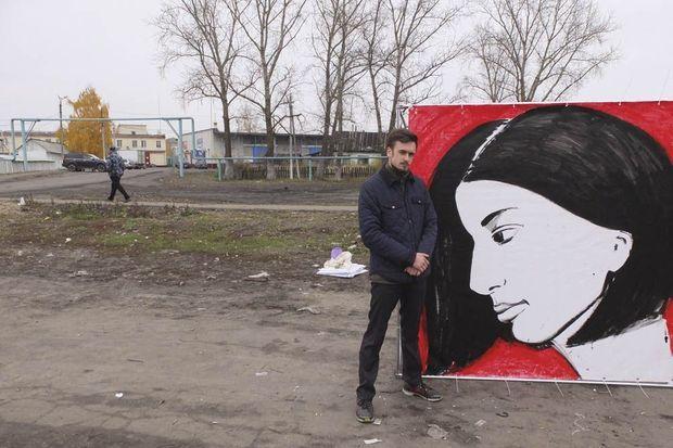 Piotr à côté d'un portrait de sa femme devant la colonie 14, près du village de Parts.