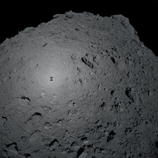 L'ombre de la sonde Hayabusa 2, et son robot franco-allemand Mascot, au-dessus de l'astéroïde Ryugu. Rapporter 10 grammes de minerai coûte 500 millions de dollars.