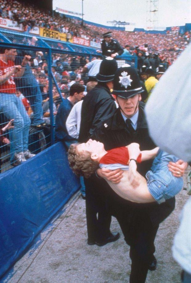 Hébété, une jeune policier porte un enfant inanimé.