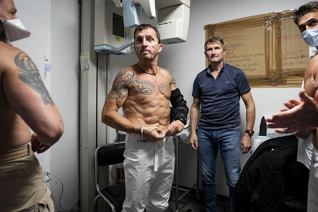 """A l'hôpital Henri-Mondor, le 7 mai. Les membres du """"commando"""" se péparent : Bruno, torse-nu; Olivier, de dos; Élian en t-shirt et Stéphane, masqué."""