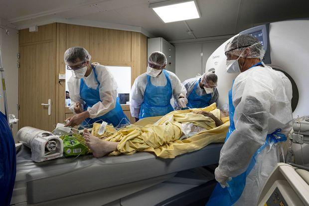 A la tête du lit, devant le scanner, Olivier est penché sur un patient. A droite, Bruno. Au bout du lit, Thierry, qui travaille à l'hôpital et au milieu, Elian.