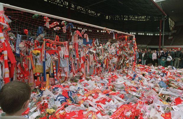 """""""À Anfield Road, les anges maudits du 'Kop' transforment leur but en sanctuaire : Liverpool pleure. Au lendemain du drame de Sheffield, à 150 kilomètres de là, les supporters du Liverpool F.c. ont rendu hommage aux martyrs du football dans leur stade d'Anfield Road. Ici, tout est rouge. Des maisons de brique voisines aux gerbes d'oeillets déposées en l'honneur des victimes. Le rouge c'est la couleur du club, avec le jaune symbolisé par les bouquets de jonquilles. Pour ce dernier adieu, les 'Rouges' se sont retrouvés sous le 'Kop' la tribune populaire qui doit son nom à une colline d'Afrique du Sud conquise par les Anglais lors de la guerre des Boers. La tragédie a gommé la rivalité des deux clubs de la ville. Les 'Bleus' d'Everton, l'équipe adverse de la banlieue, ont voulu manifester leur solidarité : dimanche, parmi les fleurs rouges et or, leurs écharpes couleur azur témoignaient de leur émotion."""" - Paris Match n°2083, 27 avril 1989"""
