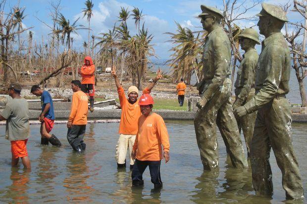 « Comme en 1944… » Plage de Palo, au sud de Tacloban, auparavant nommée Plage Imelda du temps des Marcos. Monument à la gloire du Général Mac Arthur et des Américains qui débarquèrent sur cette plage en 1944 pour libérer les Philippines de l'occupant Japonais (une des plus grandes batailles de la deuxième guerre, première fois que les Japonais utilisèrent des kamikazes). Une des statues en bronze de 3 mètres s'est affaissée durant le typhon. Des sauveteurs philippins venus de Manille y célèbrent symboliquement l'arrivée de l'aide américaine. « Nous sommes reconnaissants aux Américains de venir nous sauver pour la deuxième fois »). Ce sont les Etats-Unis qui fournissent l'essentiel de la logistique des secours.