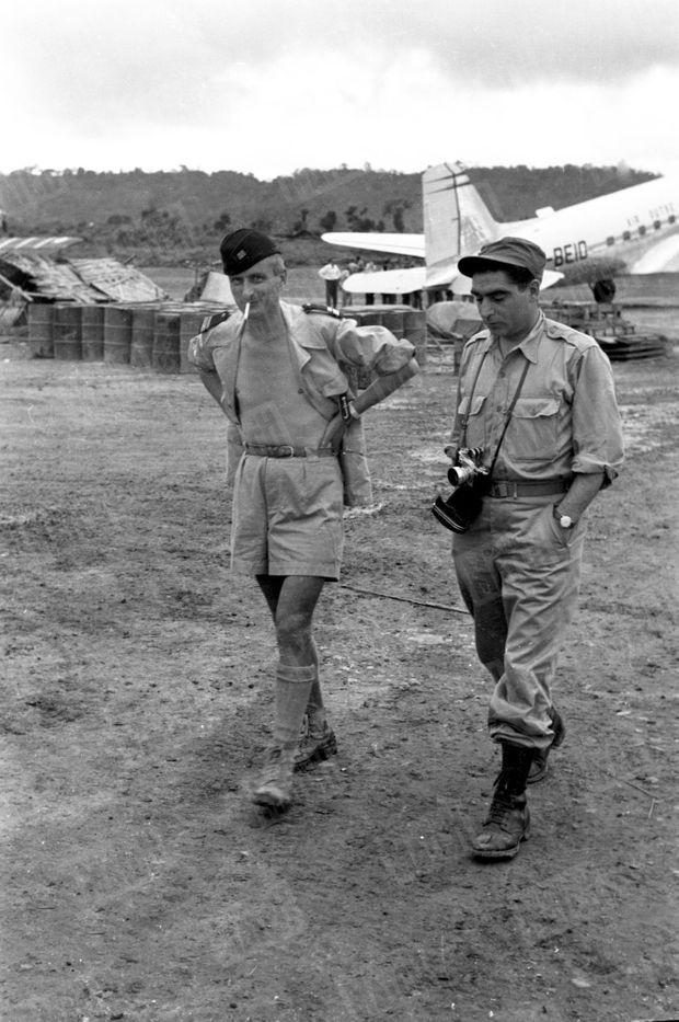 Cette photo prise par un journaliste de Match sur l'aérodrome de Luang Prabang, est la dernière image de Robert Capa, ici, en pleine conversation avec le Pr Pierre Huard, délégué du haut commandement français et de la Croix-Rouge pour le rapatriement des blessés.