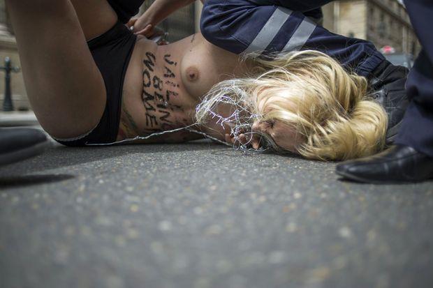 Inna Shevchenko maintenue au sol par des policiers à Paris, en juillet 2013.
