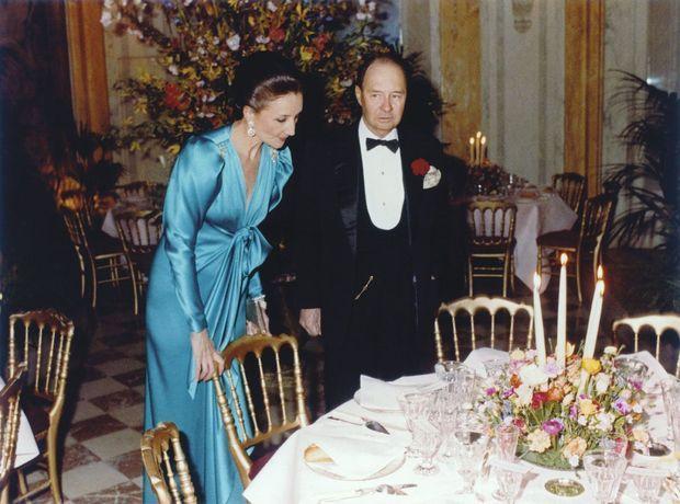 Avril 1982, au côté de son époux, le comte Edouard de Ribes. Hôtesse perfectionniste, elle contrôle le placement de table avant un grand dîner dans la serre.
