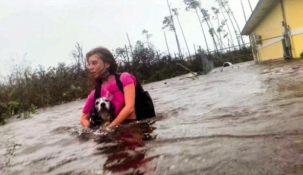 Julia, une habitante de Freeport, sur l'île de Grand Bahama, réussit à se sauver de sa maison inondée avec son chien, le 3 septembre.